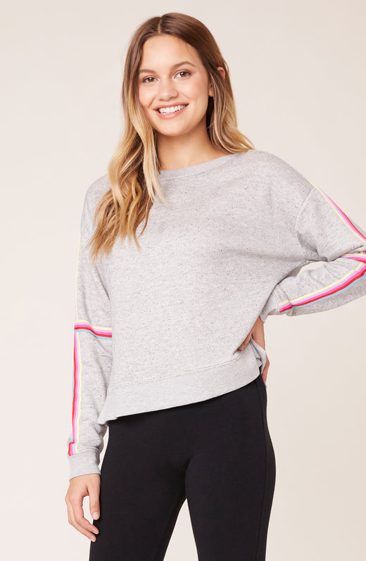 Model wearing grey pullover sweater with pink contrast stripe