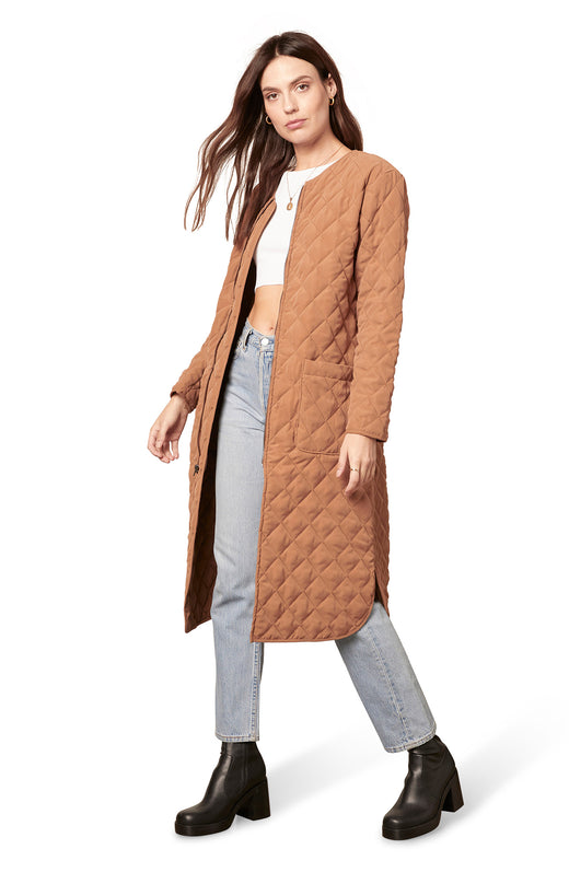 dark camel diamond-quilted collarless coat with a zip front and pockets.