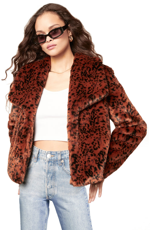 rust / burnt orange color soft leopard print faux fur jacket with a draped open front silhouette and pockets.