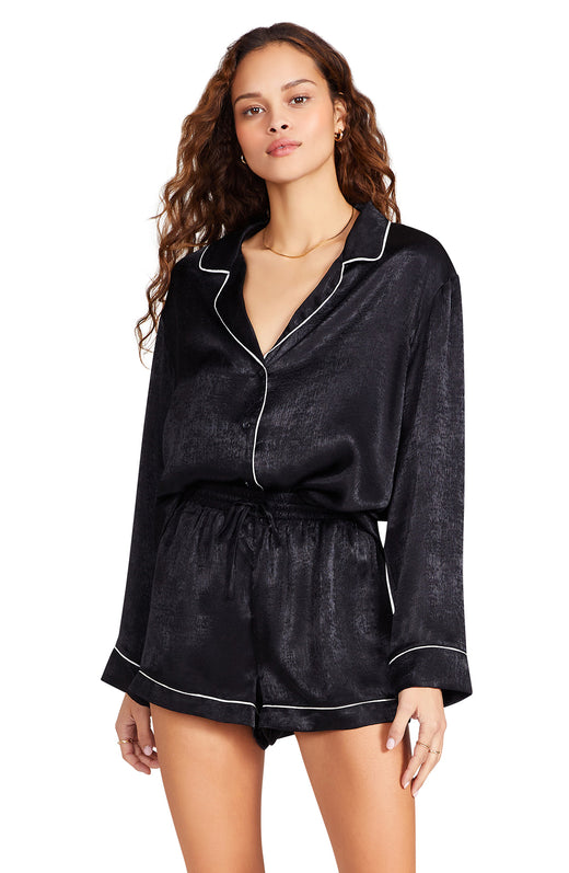 black colored silky textured satin pajama short with a elasticized tie waist and contrast piping detail.