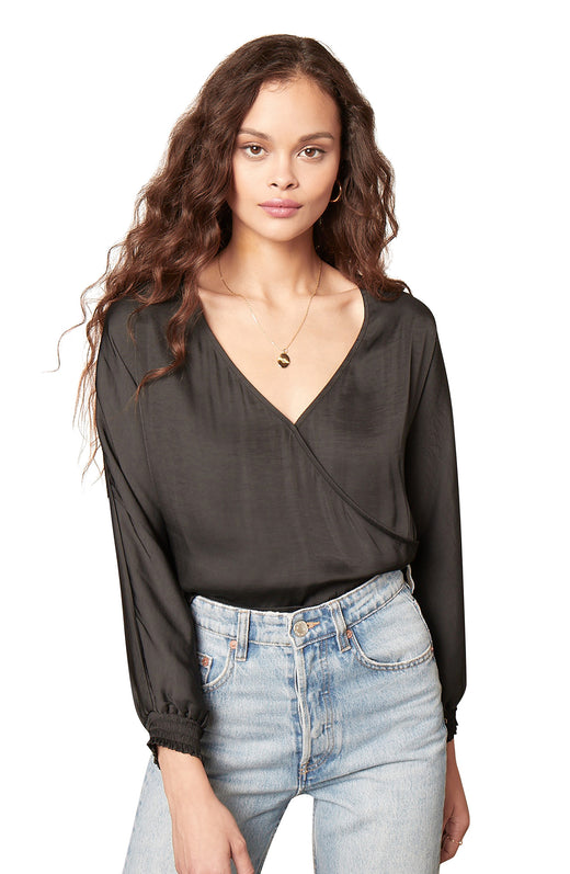 black color dolman sleeve dull satin blouse with a cross over V-neckline, fitted waistband, and smocked sleeve cuffs.