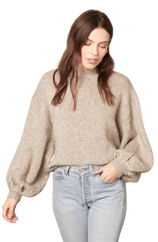 heather grey soft lurex knit mockneck sweater with balloon sleeves, woman standing with head down and hand in pocket