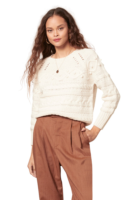 front view of textural multi-stitch pattern cable knit sweater. model looking into camera with hand inside brown trousers