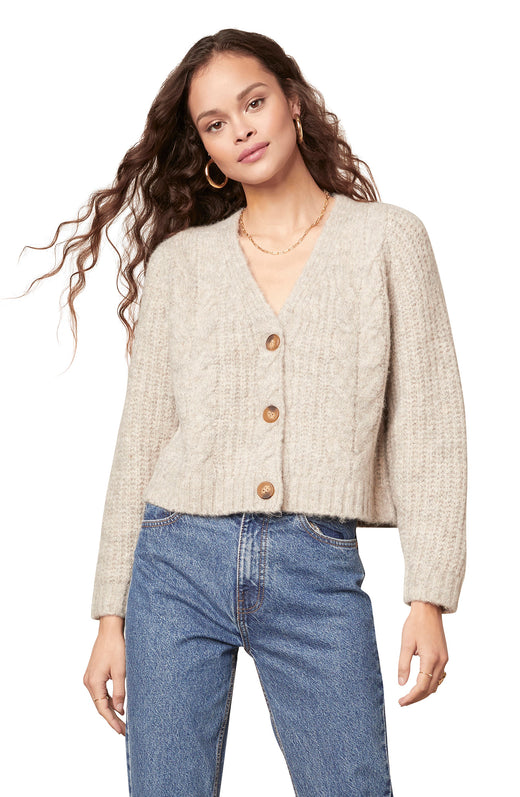 light tan colored marled yarn cable knit cardigan with a three button closure and V-neckline.