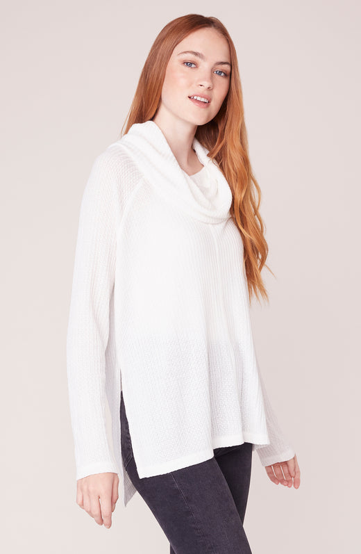 Model wearing cowl neck long sleeve ivory sweater