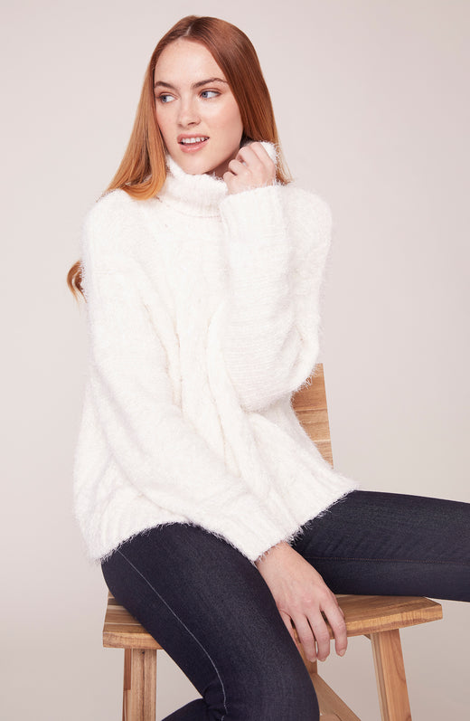Model sitting and wearing ivory turtle neck sweater