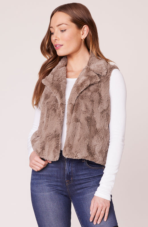 Model wearing tan fuzzy faux fur vest