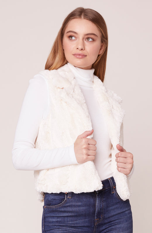 Model wearing ivory fuzzy faux fur vest