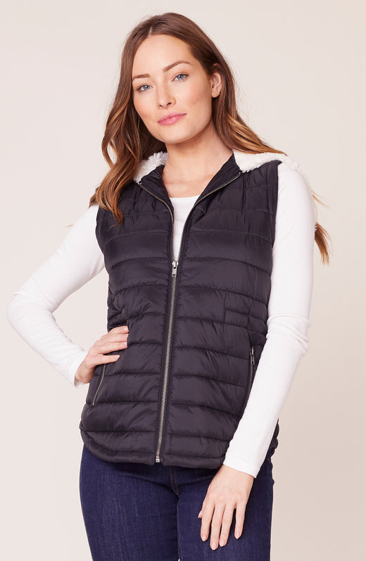 Model wearing black puffer vest with sherpa lining