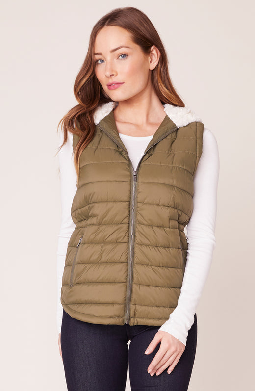 Model wearing green puffer vest with sherpa lining