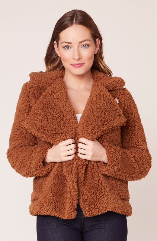 Model wearing fuzzy tan jacket