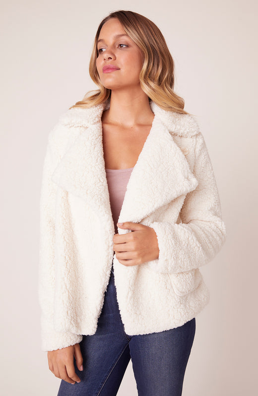 Model wearing fuzzy white faux fur jacket