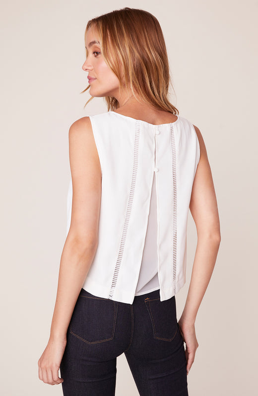 Back view of model wearing sleeveless blouse with vent back detail