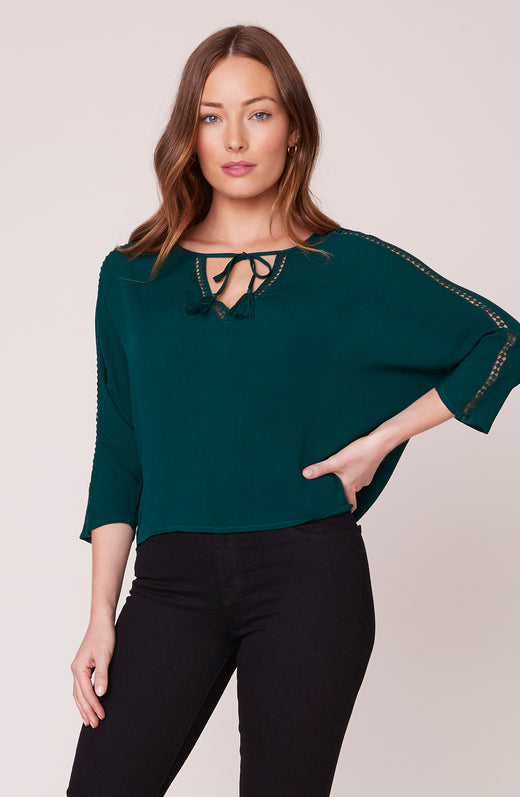 Model wearing green 3/4 sleeve top