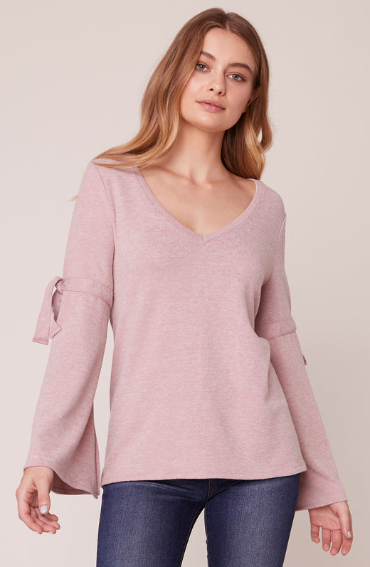 Model wearing pink bell sleeve sweater