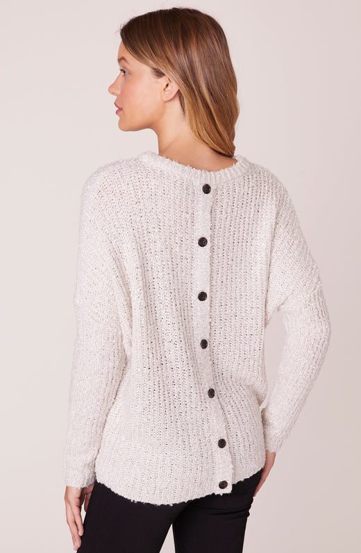 Back view of model wearing sweater with button back