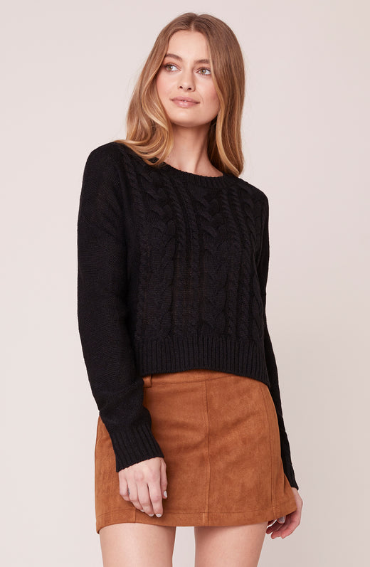 Model wearing black cable knit sweater
