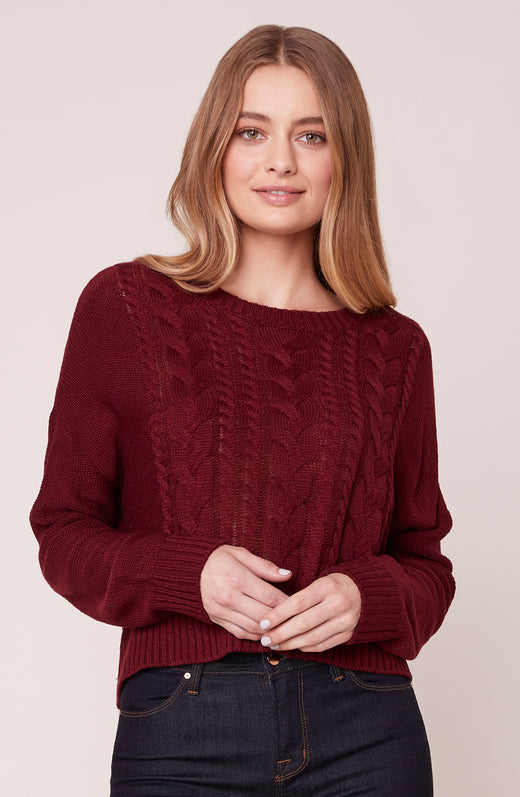 Model wearing burgundy cable knit sweater