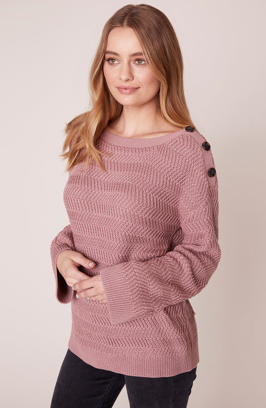 Model wearing pink sweater with shoulder button detail