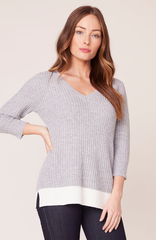 Model wearing grey and white color block sweater