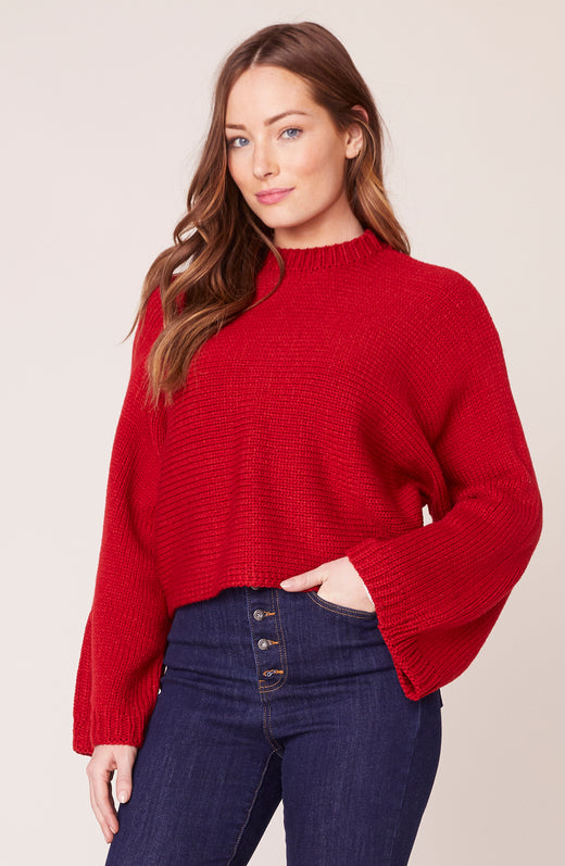 Model wearing red bell sleeve sweater with mock neck