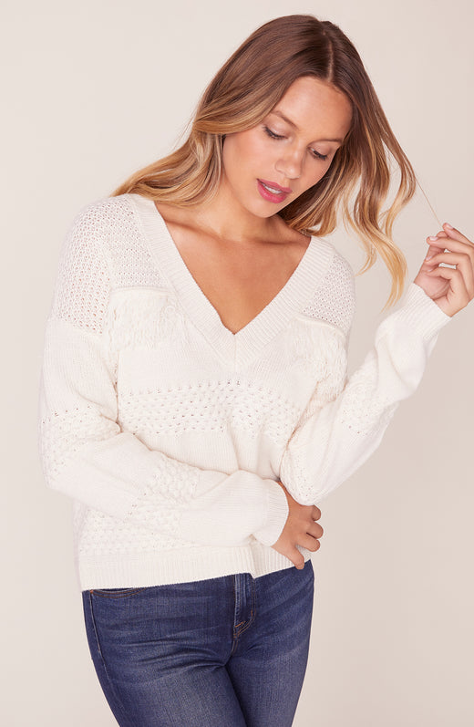 Model wearing ivory sweater with fringe