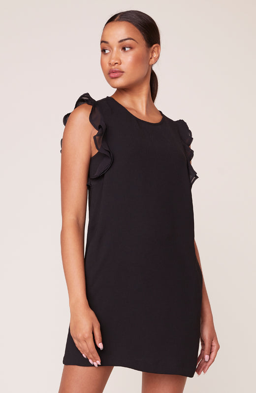 Model wearing black shift dress with ruffled sleeves