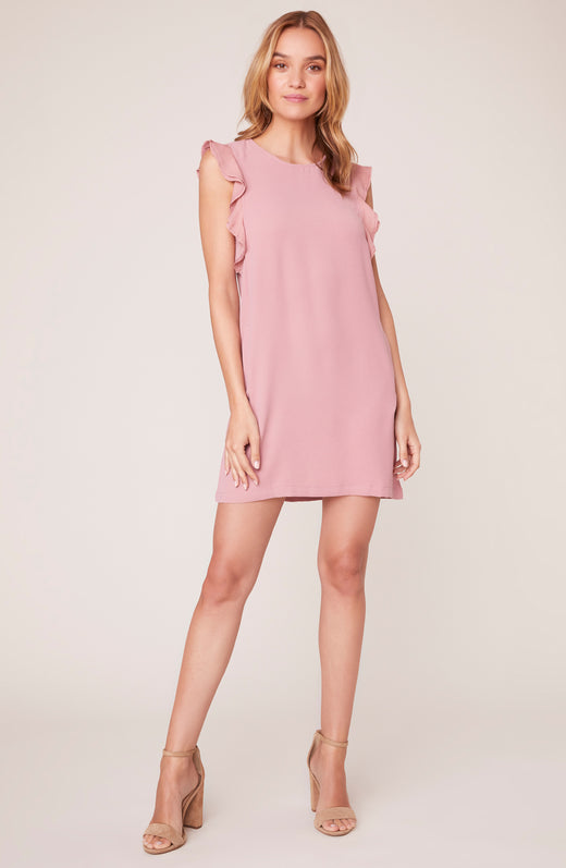 zoomed out view of model wearing pink shift dress with ruffled sleeves
