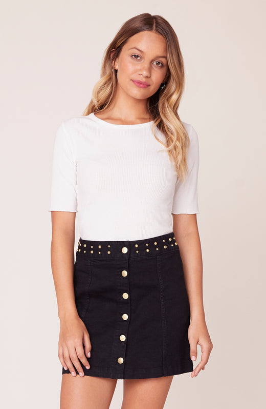 Model wearing black denim skirt with studded waist