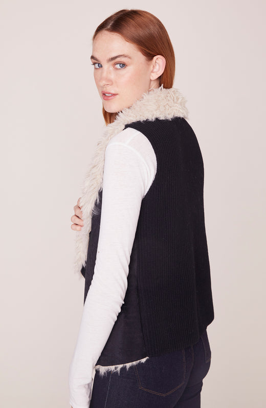 Side view of model wearing black shearling vest