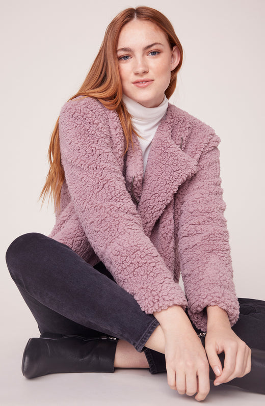 Model sitting wearing pink sherpa jacket