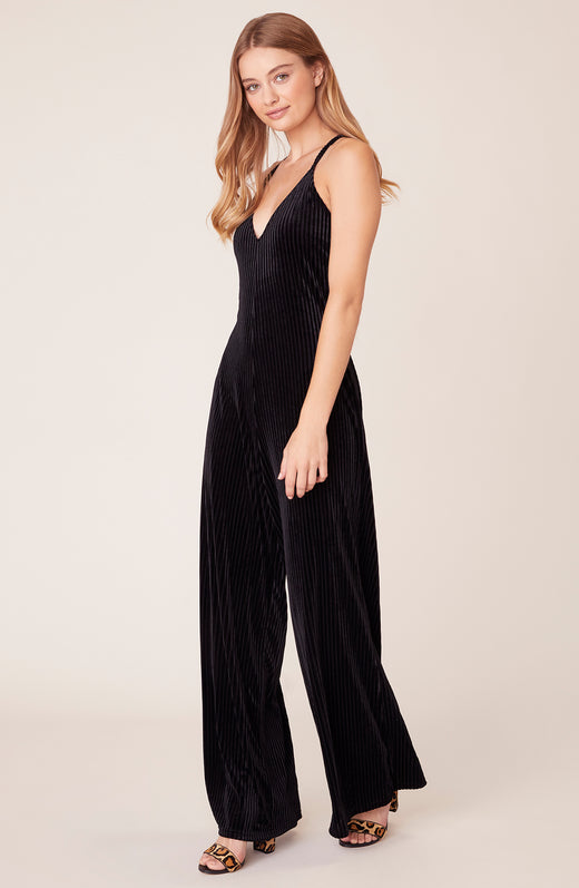 Front view of model wearing black velvet jumpsuit