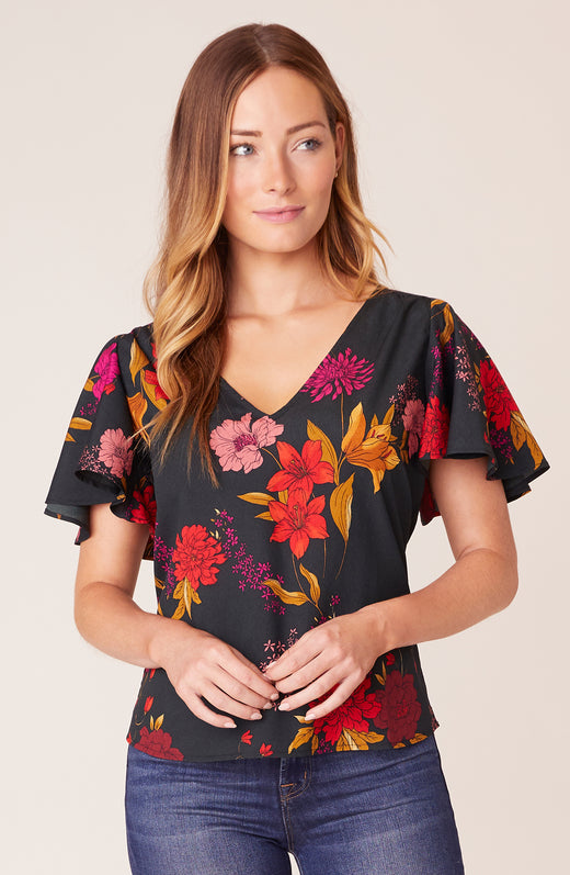 Model wearing floral flutter sleeve top