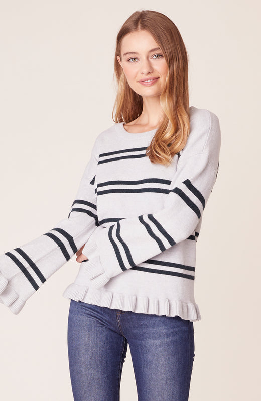 Front view of model wearing striped ruffle sweater
