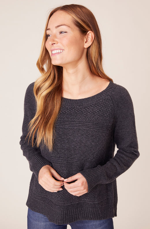 Front view of model wearing grey sweater