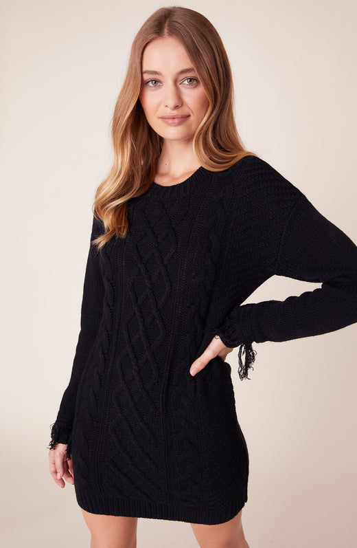 Front view of model wearing black cable knit sweater dress