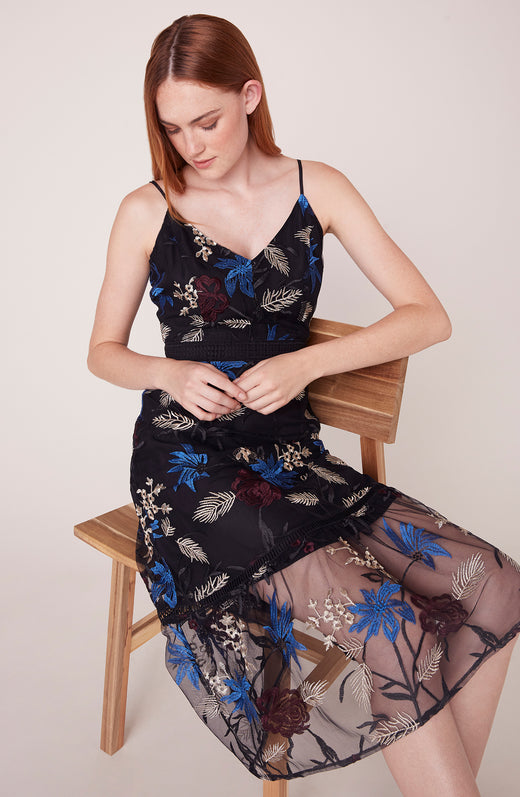 Model sitting wearing black embroidered dress