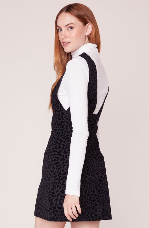 Side view of model wearing leopard pinafore dress