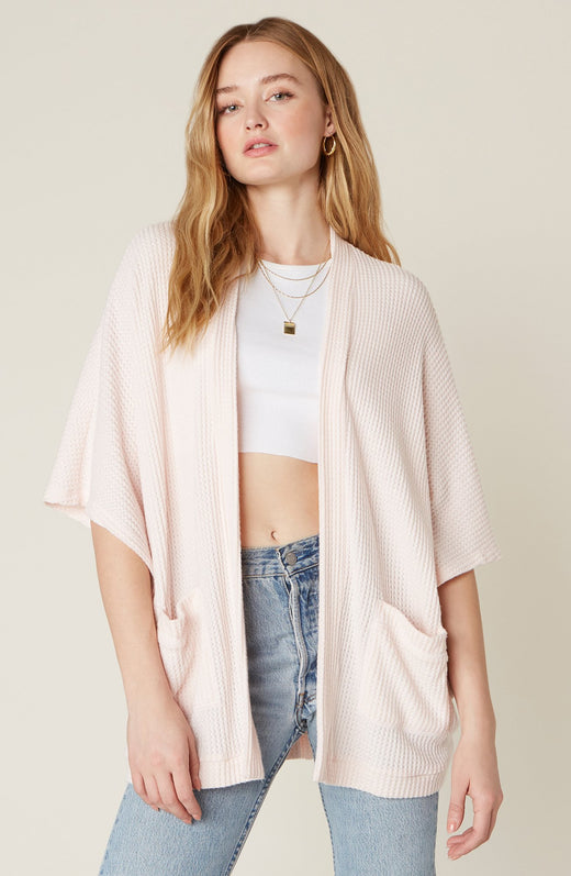 Model wearing light pink waffle knit cardigan