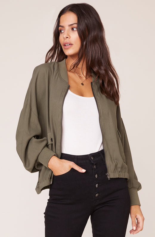 Model wearing sage green bomber jacket