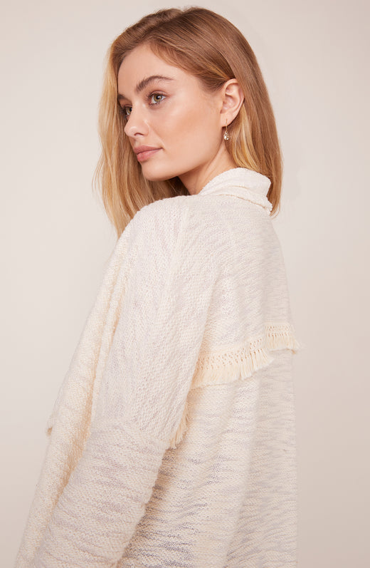 Back view of model wearing fringed cardigan sweater