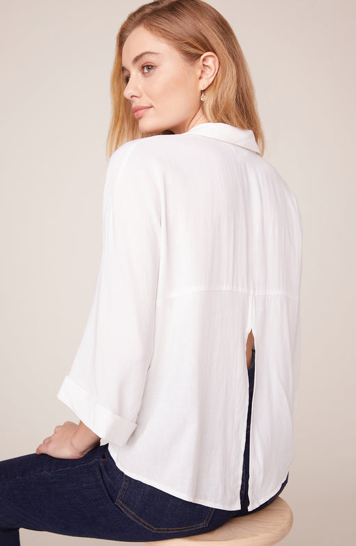 Back view of model wearing button up shirt with slit back