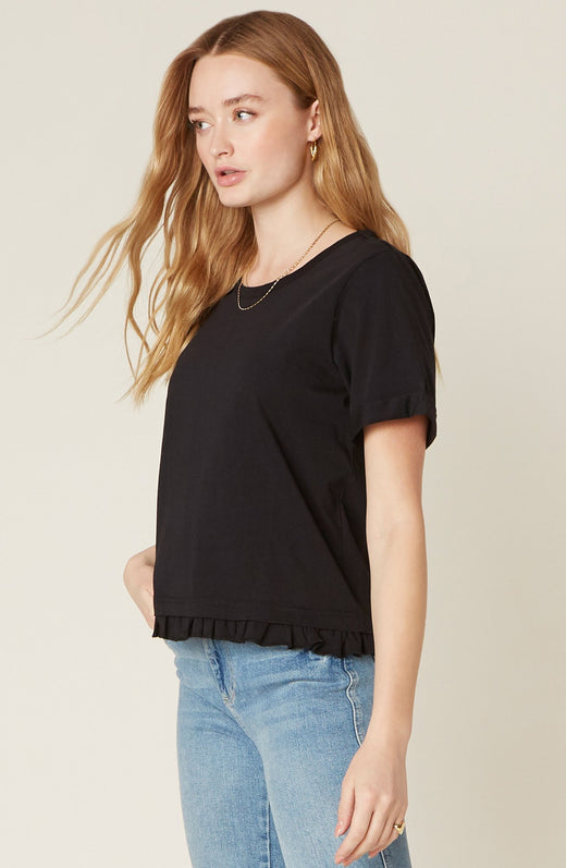 Model wearing black boxy top with ruffled hemline