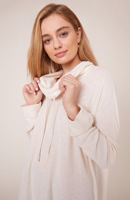 Model wearing ivory cowl neck top