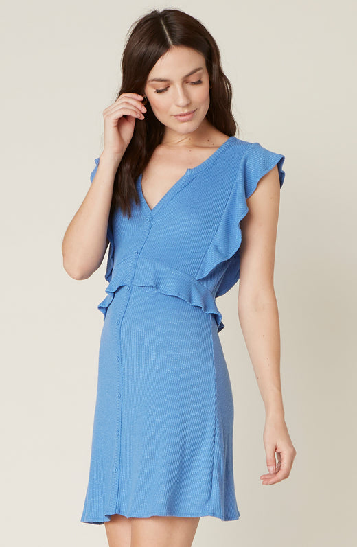 Model wearing blue dress with ruffle detail