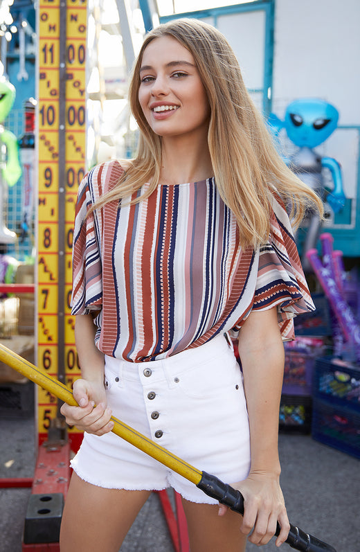 Model wearing striped top playing carnival games