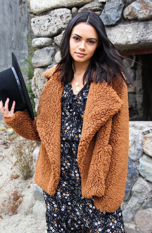 Blogger wearing fuzzy tan jacket with budding romance dress