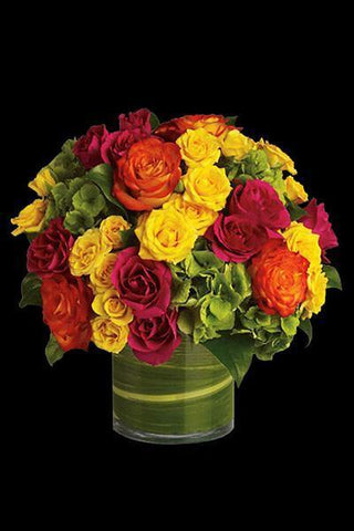 Colorful arrangement of Roses and Hydrangeas arranged in a round vase.