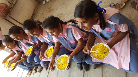 Students at Fior Di Loto, wearing their pink and purple school uniforms, sit in a row enjoying some fresh, hot lunch: bowls of bountiful yellow rice!