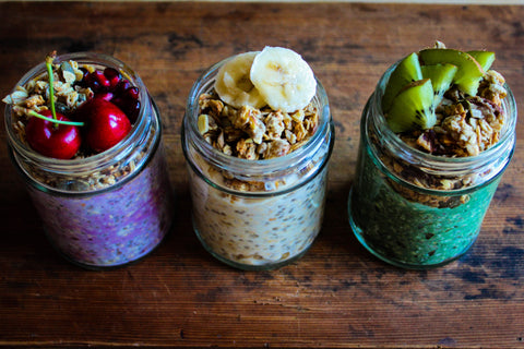"""Three glass mason jars sitting in a row; each contains one of Gem's beautiful, """"extra"""" overnight oat recipes. From left to right: Chill-out Cherry (added cacao powder topped with fresh cherries); Maca Mood Booster (added Maca powder topped with chopped banana); and Green Energy Boost (added spirulina topped with fresh kiwi)."""